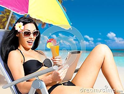 Happy woman on the beach with ipad