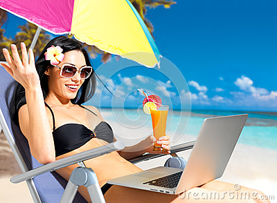 Happy woman on the beach with a laptop