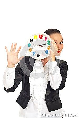Happy woman behind clock show five fingers