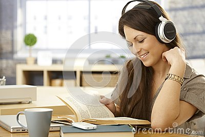 Happy woman with book and headphones