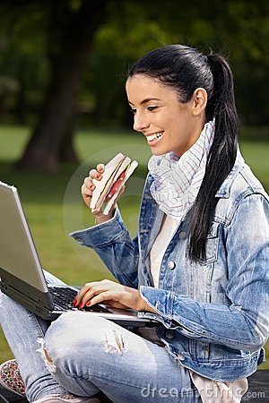 Happy woman browsing internet in park eating
