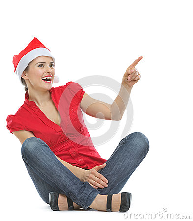 Happy woman in Christmas hat sitting on floor