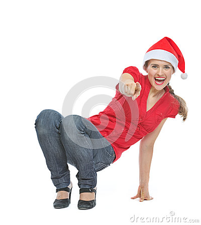 Happy woman in Christmas hat squatted on floor