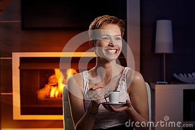 Happy woman with coffee in cosy room