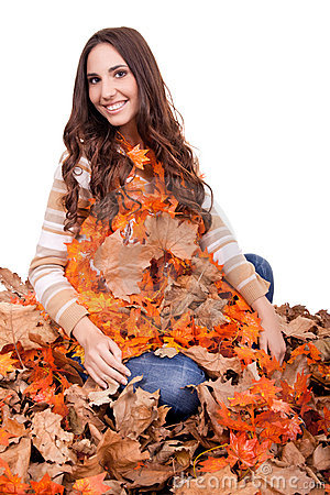 Happy woman covered with autumn leaves