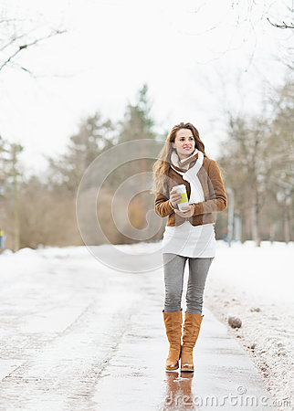 Happy woman with cup of hot beverage walking in winter park