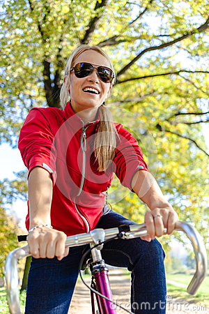 Happy woman cycling on bicycle in park