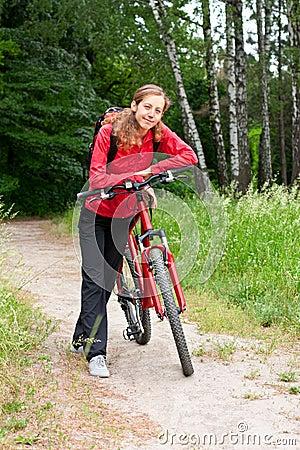 Happy woman cyclist on a bicycle walk