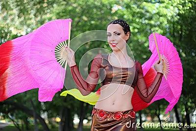 Happy woman dances with veil fans