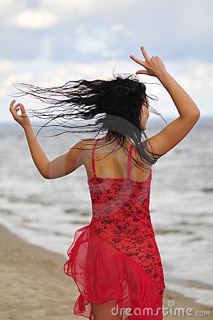 Happy woman dancing on the beach