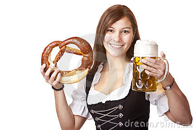 Happy woman in Dirndl holds beer stein and pretzel