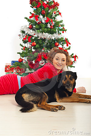 Happy woman with dog lying by Xmas tree