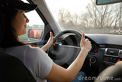 Happy woman driving car inside