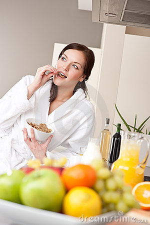 Happy woman eat cereals for breakfast in kitchen