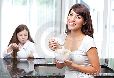 Happy woman eating breakfast cereal with daughter