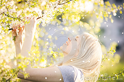 Happy woman enjoying spring, nature, falling petal