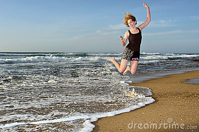 Happy woman flies with with mobile phone on beach