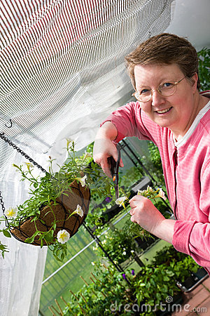 Happy Woman Gardens in her greenhouse