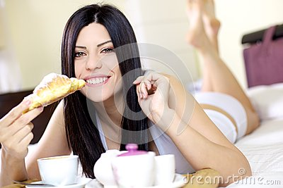 Happy woman having breakfast in bed at home