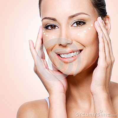 Happy woman with healthy face applying cream under the eyes