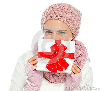 Happy woman hiding behind Christmas present box