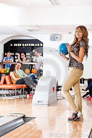 Happy Woman Holding Bowling Ball in Club
