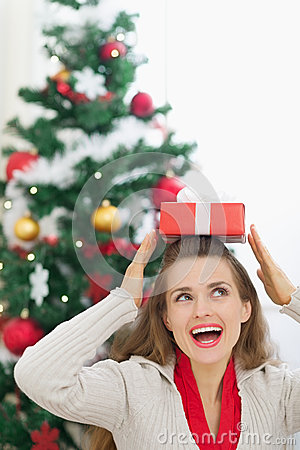 Happy woman holding Christmas present box on head