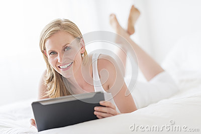 Happy Woman Holding Digital Tablet While Lying On Bed