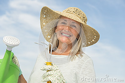 Happy Woman Holding Gardening Equipment Against Sky