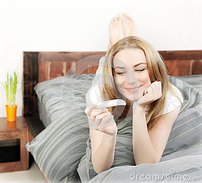 Happy woman holding pregnancy test