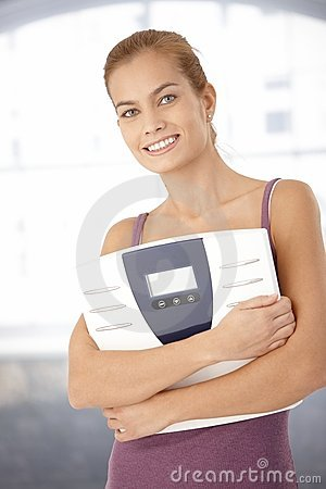 Happy woman holding scale in arms
