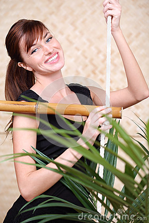 Happy woman holds on bamboo rope ladder