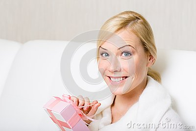 Happy woman holds a gift with pink ribbon