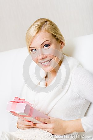 Happy woman holds a present with pink ribbon