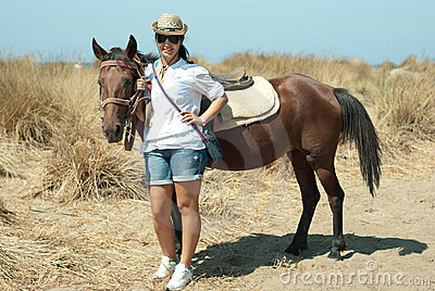 Happy woman with horse on beach