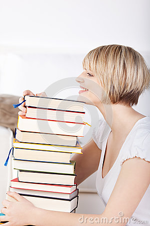 Happy woman with a huge stack of books