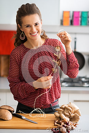 Free Happy Woman In Kitchen Stringing Mushrooms Together Royalty Free Stock Image - 64162826