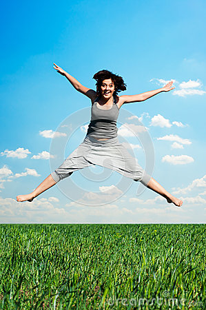 Happy woman jumping at the field