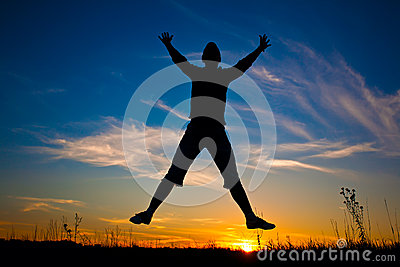 Happy woman jumping over the sunset blue sky