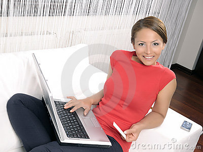 Happy woman looking at camera with laptop