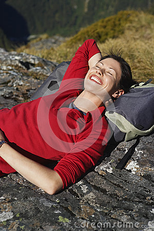 Happy Woman Lying On Boulder With Backpack