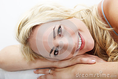 Happy woman lying with head on arms