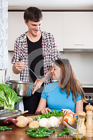Happy woman and man cooking vegetables