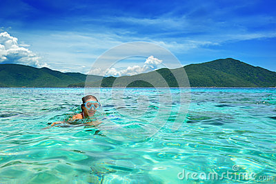 Happy woman with a mask floating in the azure tropical sea