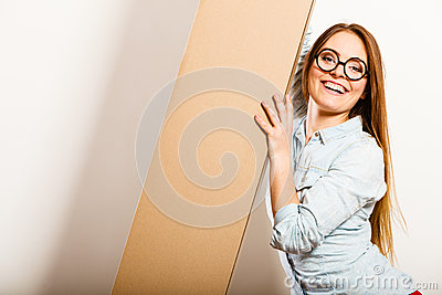 Happy woman moving into apartment carrying box. Stock Photo