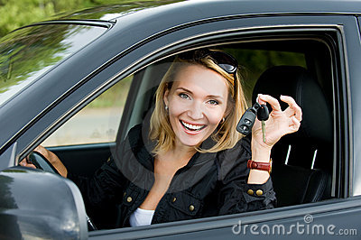 Happy woman in the new car with keys