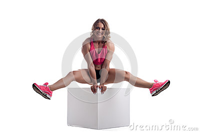 Happy woman with perfect body sit on cube