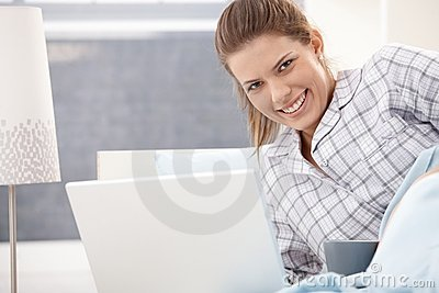 Happy woman in pyjama using laptop