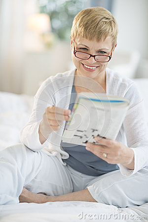 Happy Woman Reading Book On Bed
