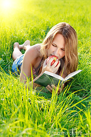 Free Happy Woman Reading Book With Apple In Hand Stock Photo - 24020760